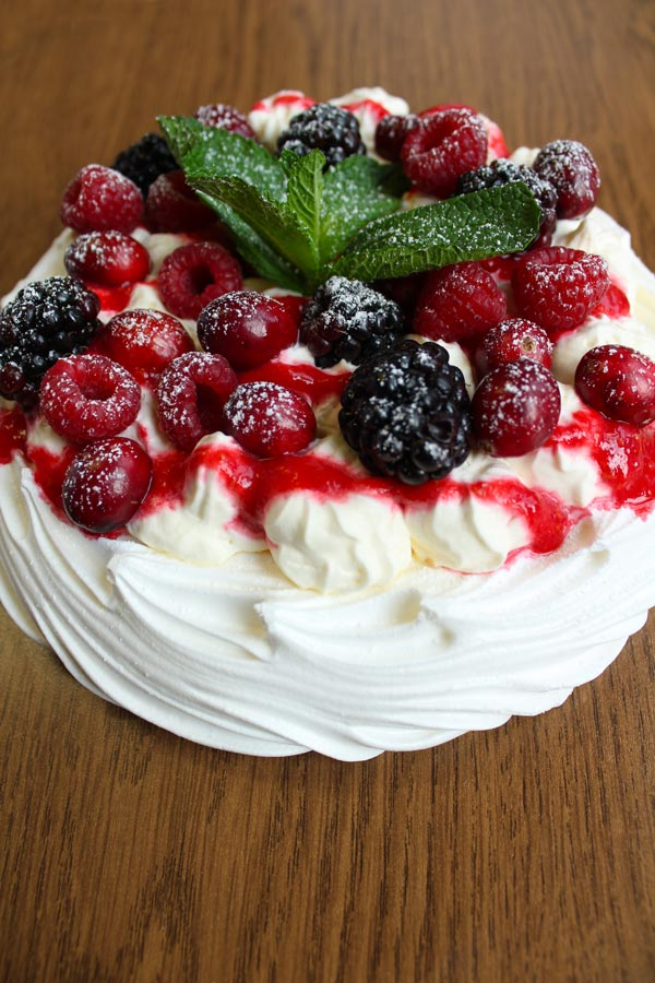 Vegan pavlova topped with mixed berries and a mint sprig