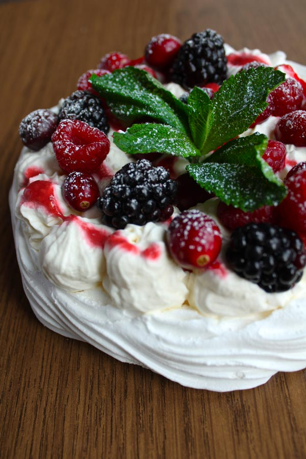 vegan pavlova with berries, whipped cream and a sprig of mint on top