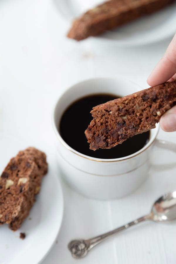 piece of biscotti being dipped into chocolate sauce