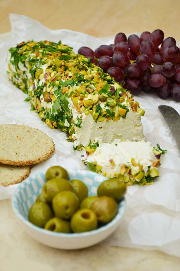 Cheese log topped with pistachios, beside some olives, oatcakes and grapes