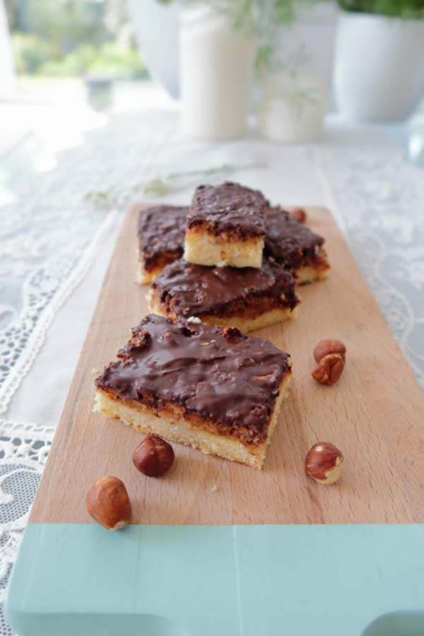 Slices of chocolate hazelnut bars on a board with hazelnuts scattered around