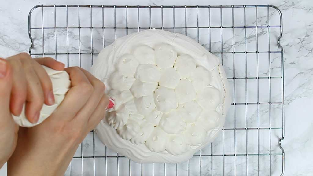 piping whipped cream onto the pavlova