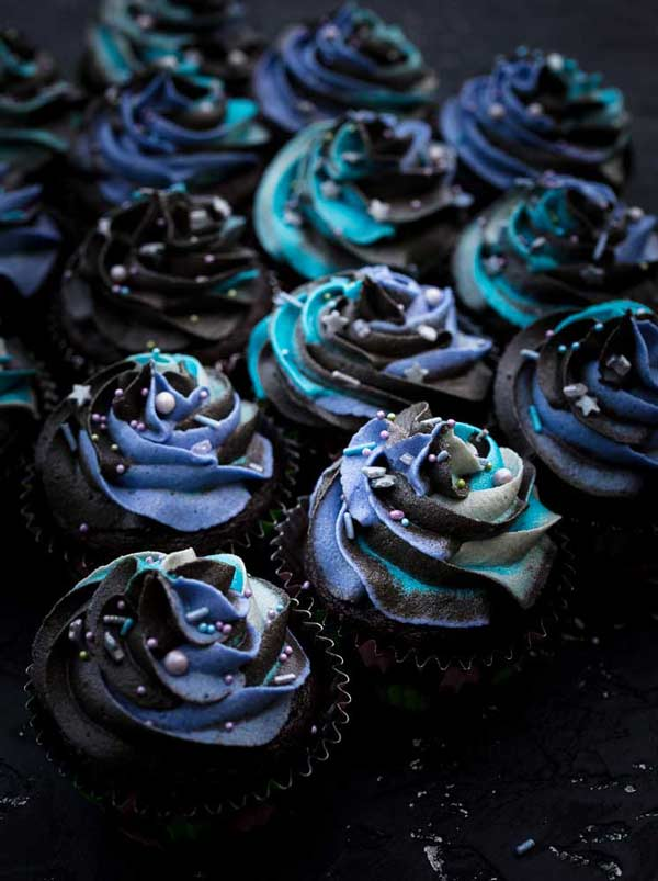 Close up of cupcakes with purple, black and blue icing