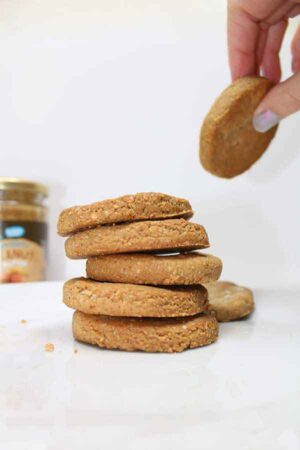 Hand lifting a peanut butter cookie from a stack