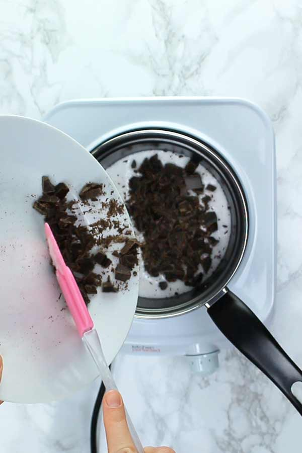 pouring chopped chocolate into pan