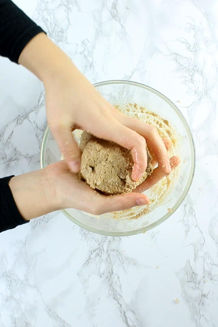 Hands holding a ball of dough for peanut butter chocolate bars