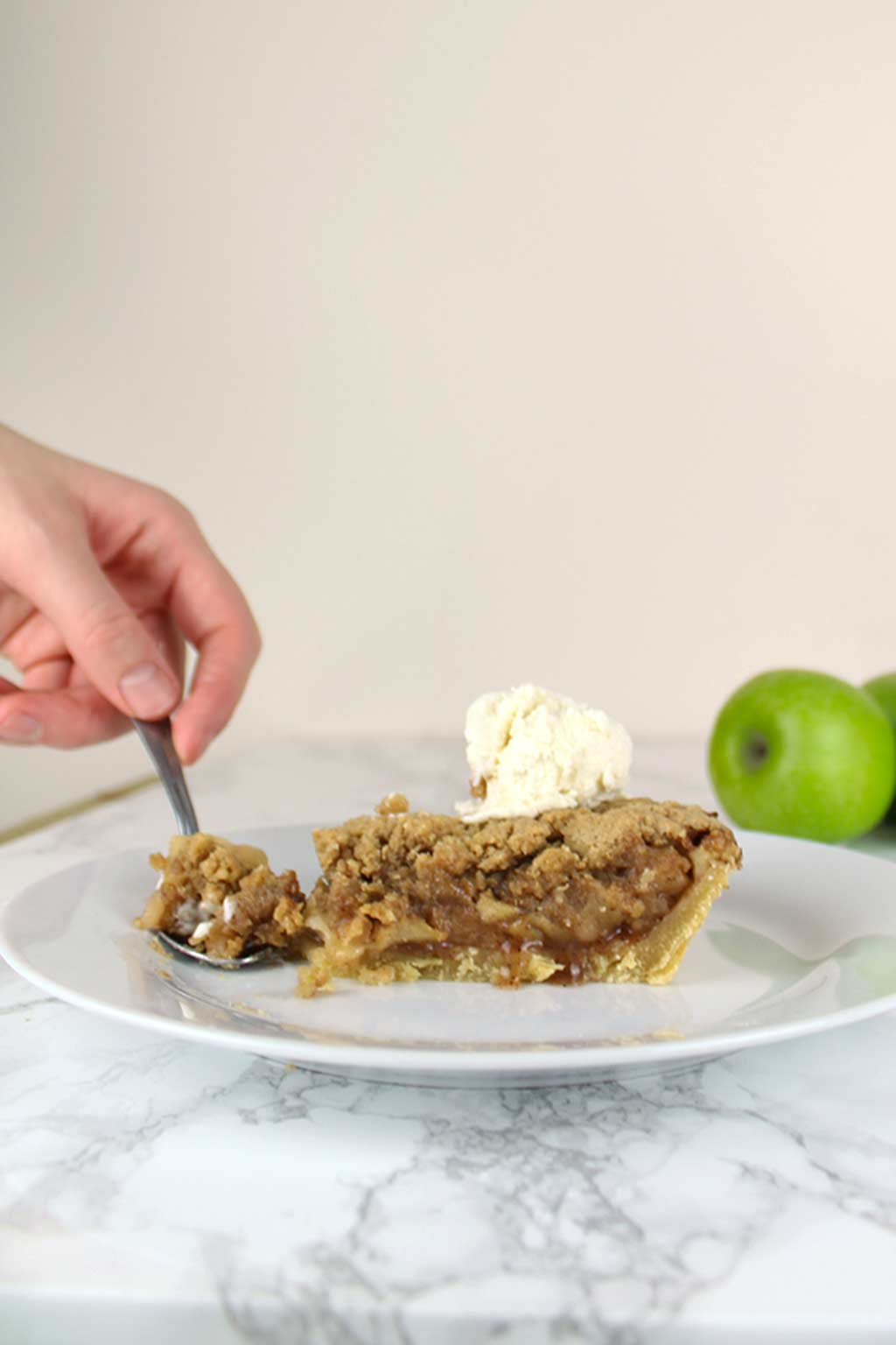 spoon cutting into a slice of vegan apple crumble pie on a plate