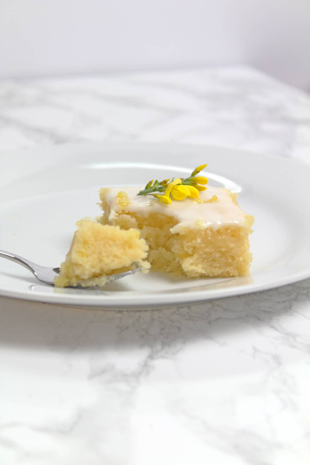 slice of lemon cake with a spoonful of cake beside it