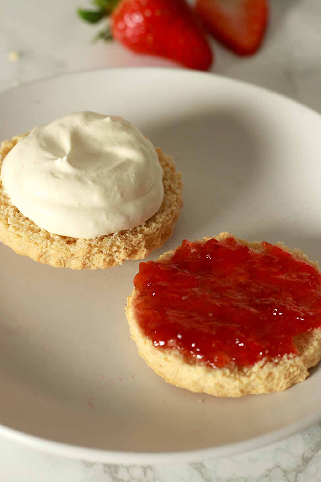 Two Halves Of A Scone On A White Plate. One Has Jam On It And The Other Has Cream On It.