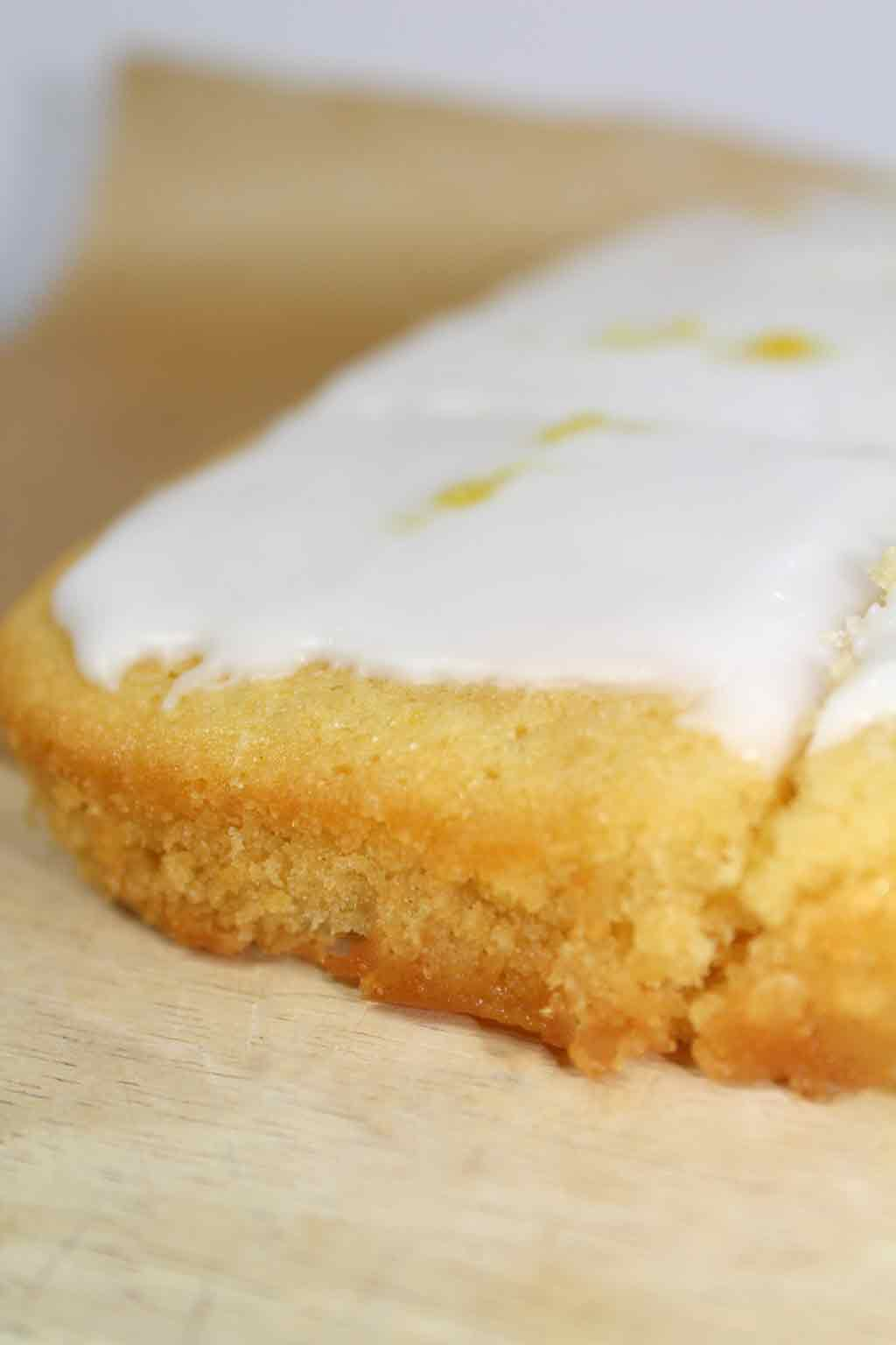 close up of lemon drizzle cake with icing