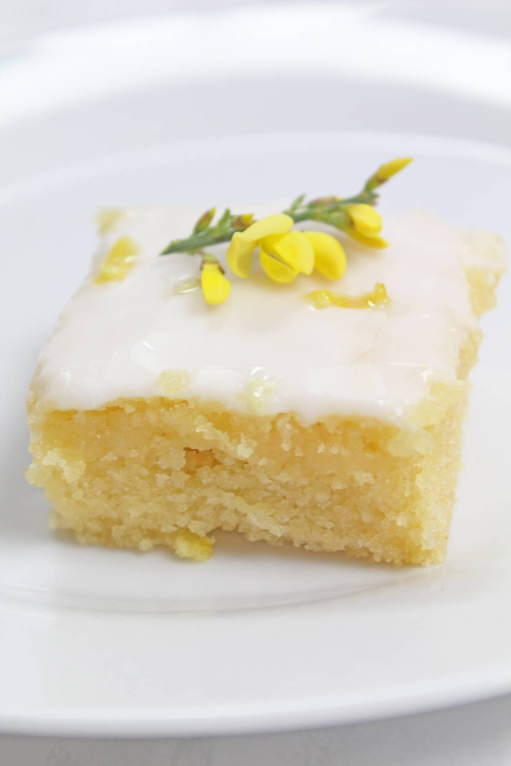 A square slice of cake with a yellow flower on top