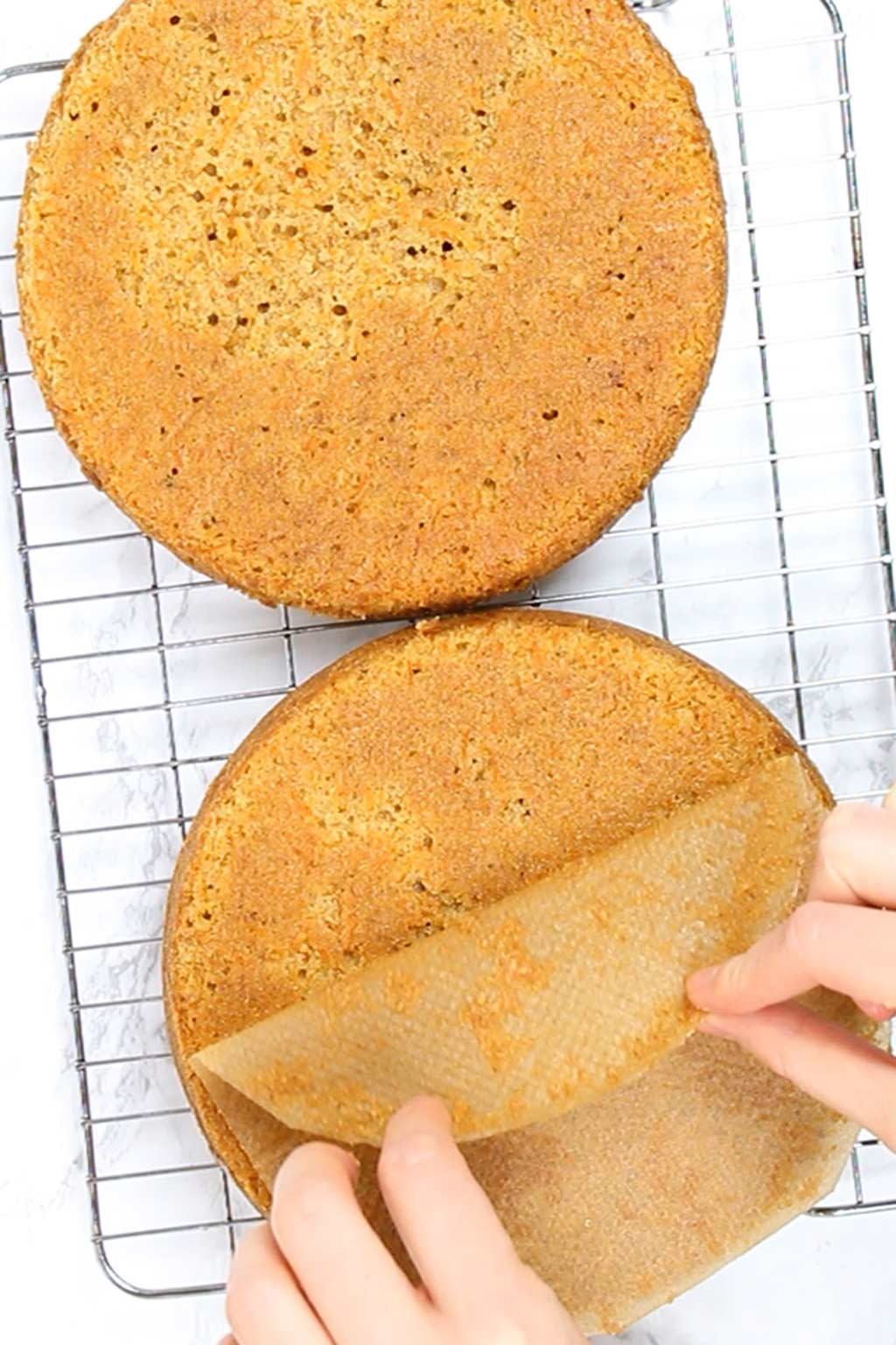 peeling baking paper off of cakes on a cooling rack