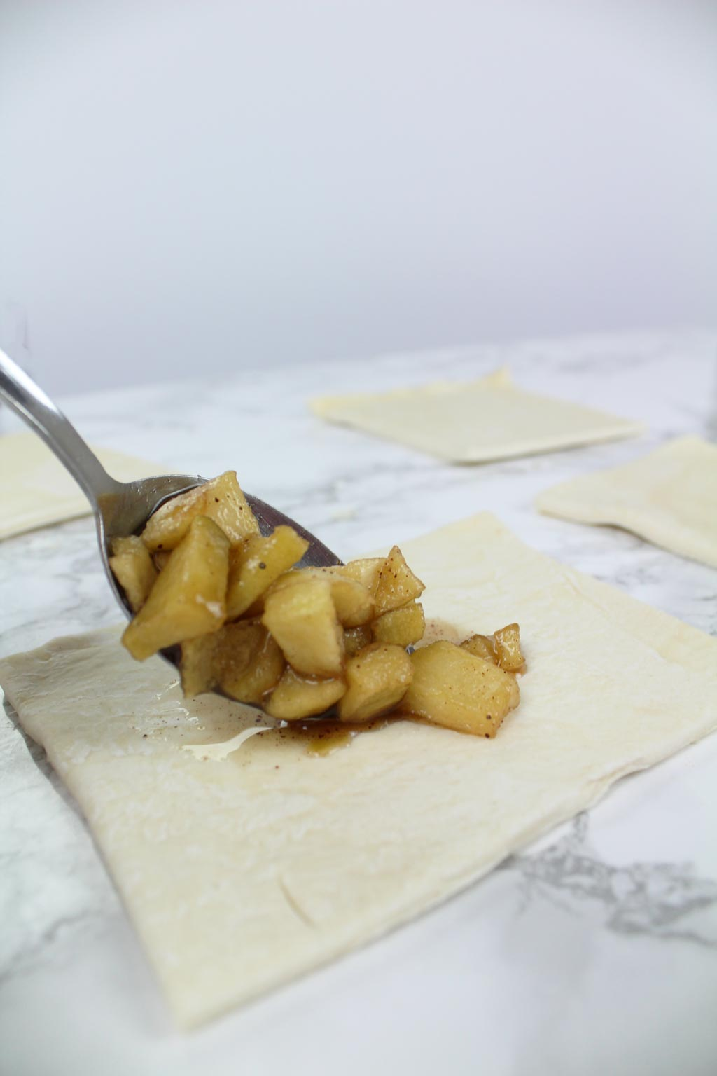 putting apple filling into puff pastry squares