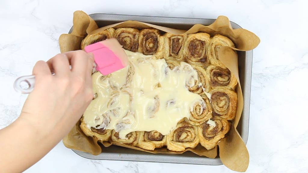 topping the cinnamon rolls with cream cheese icing