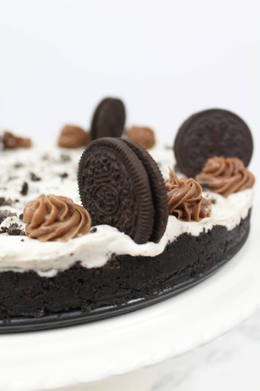 no bake Oreo cheesecake on cake stand, up close