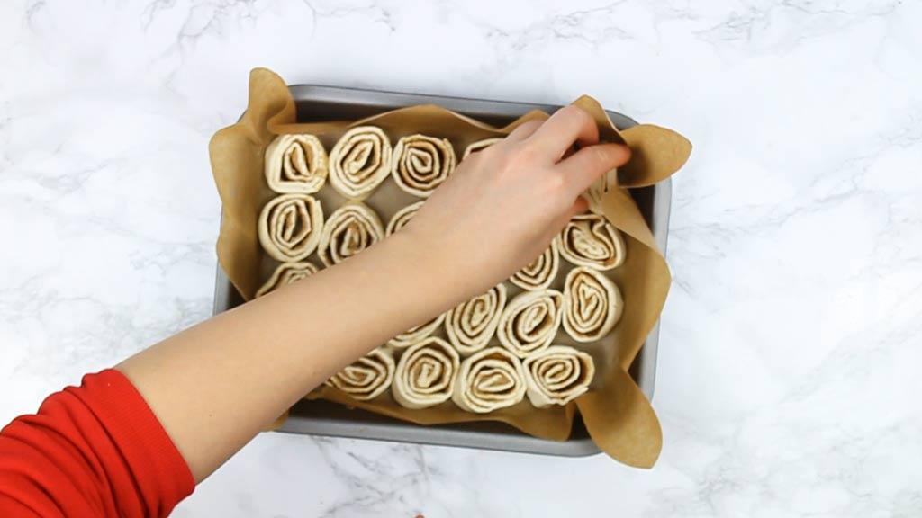 Placing cinnamon rolls into dish for baking