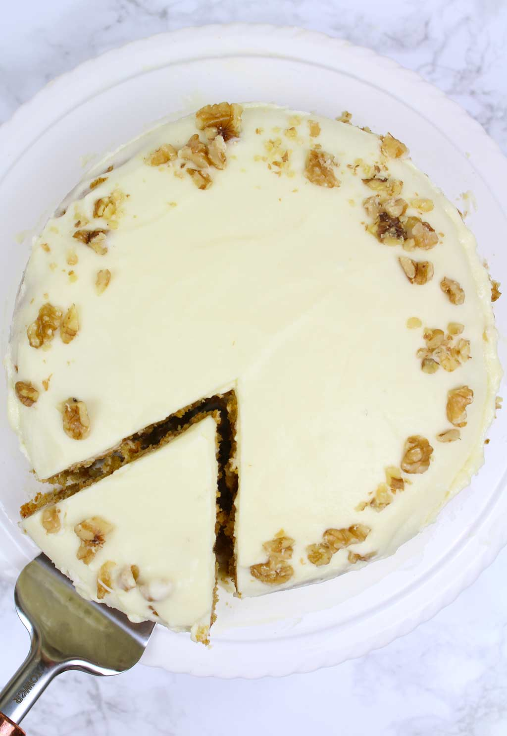 overhead shot of carrot cake with a slice taken out of it