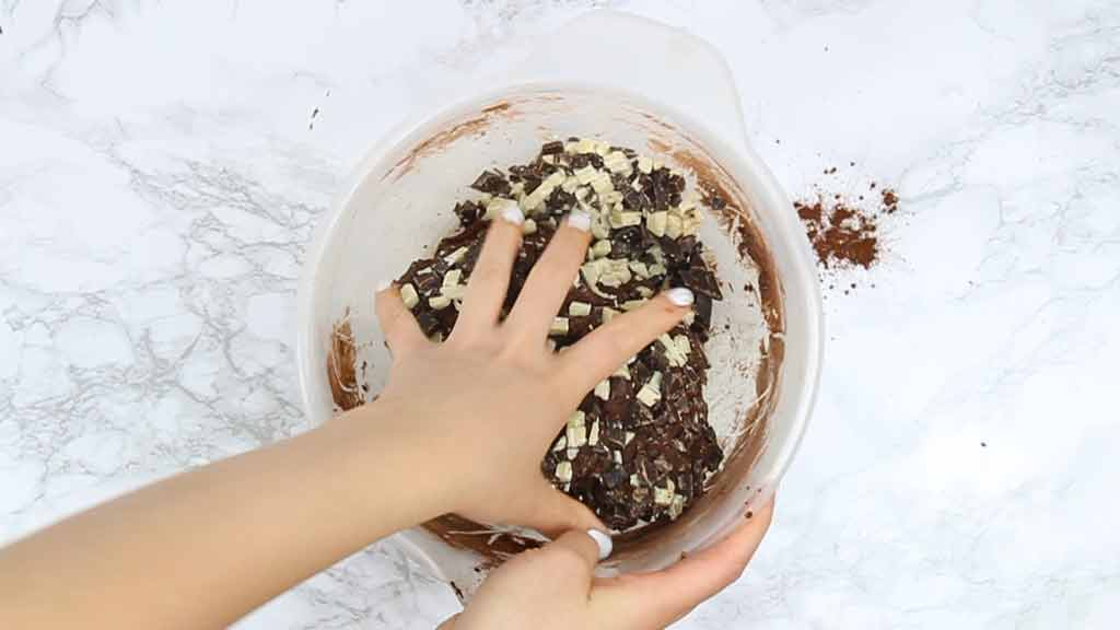 adding chocolate chunks to the cookie dough