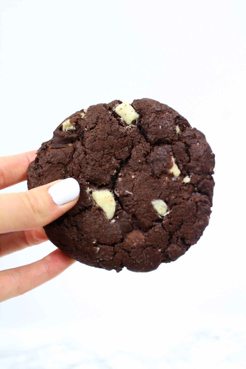 a hand holding a vegan double chocolate cookies
