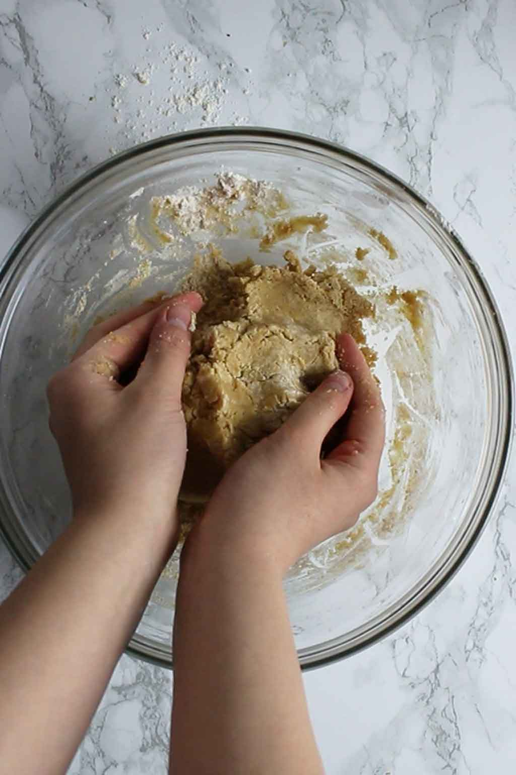 two hands holding a large ball of cookie dough in a bowl