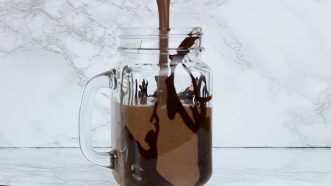 pouring cookies and cream milkshake into glass