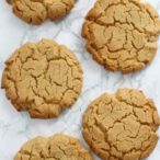 overhead shot of 5 vegan peanut butter cookies on a white surface