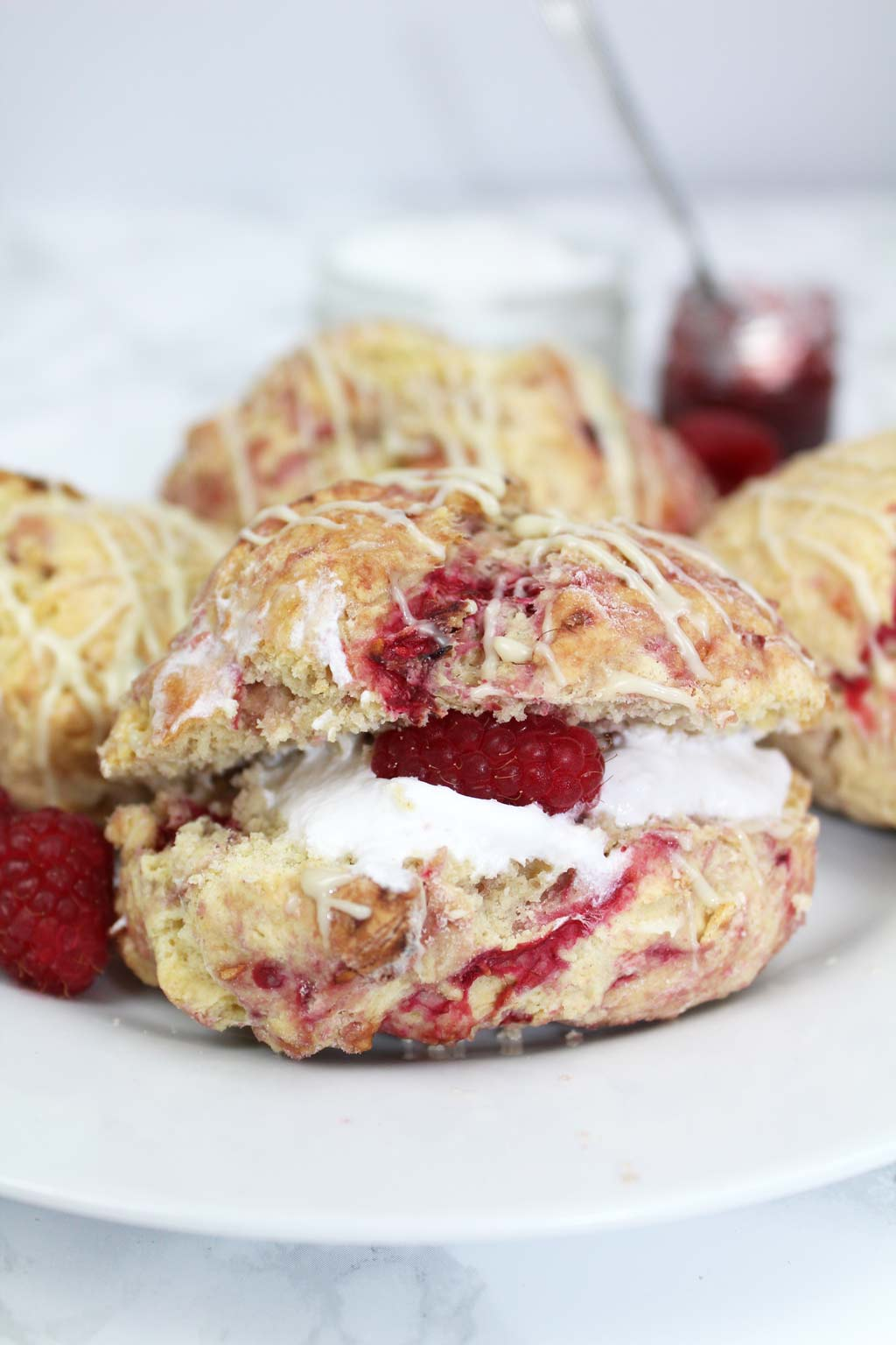 Raspberry white chocolate scone on a plate with whipped cream in the middle