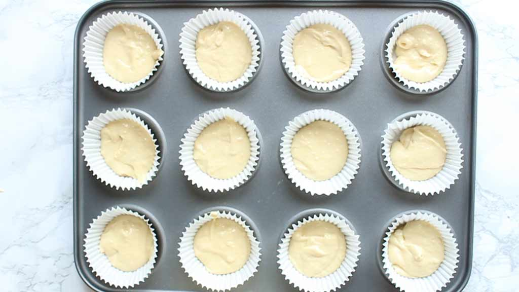 cupcake batter in liners on a tray