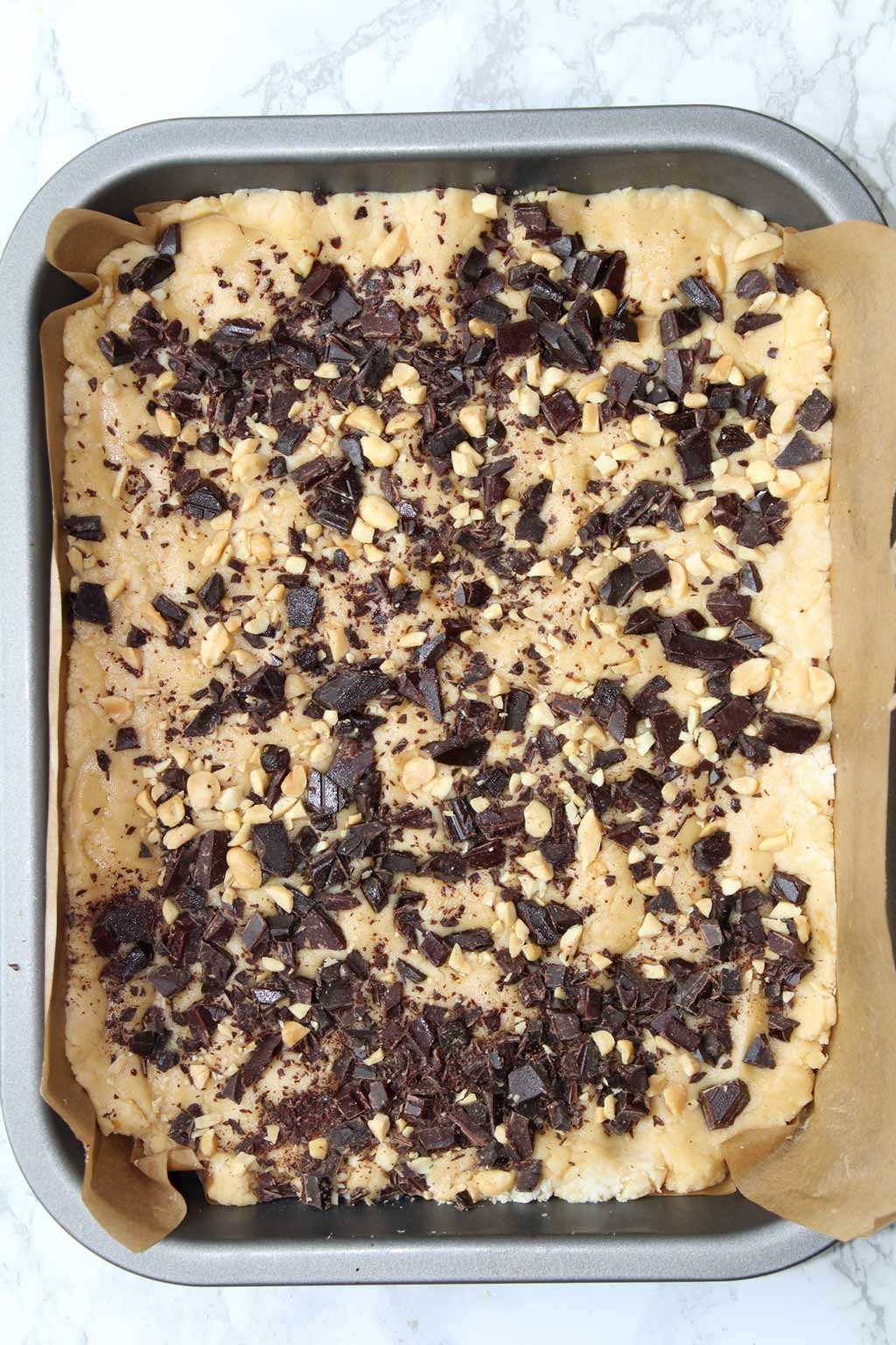 fudge in tray with chopped chocolate and chopped peanuts on top