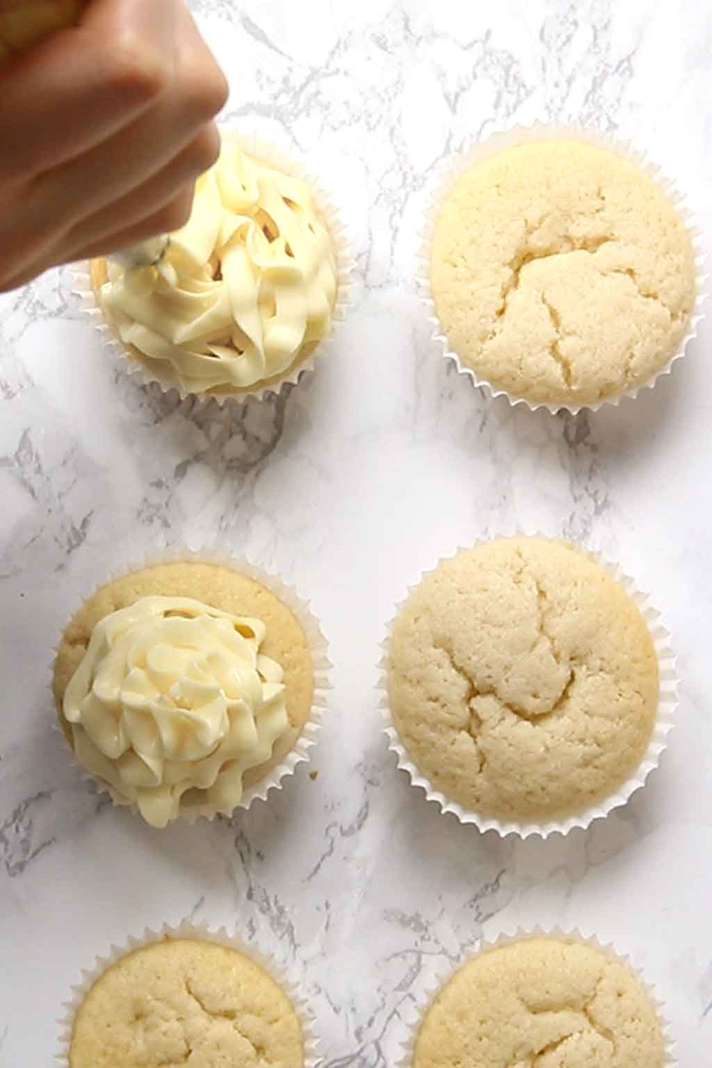 Piping frosting onto cupcake