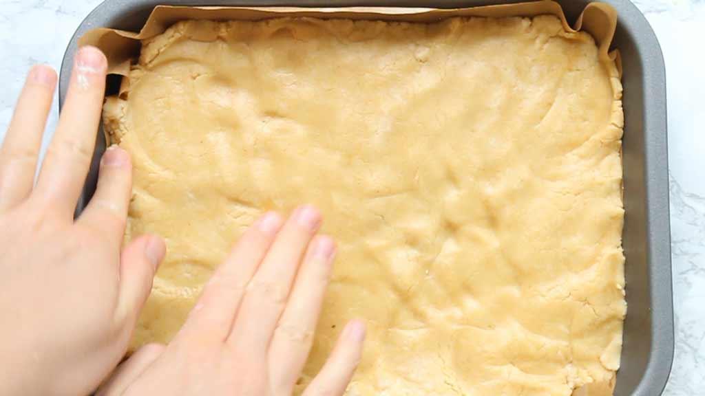pressing fudge into the tin
