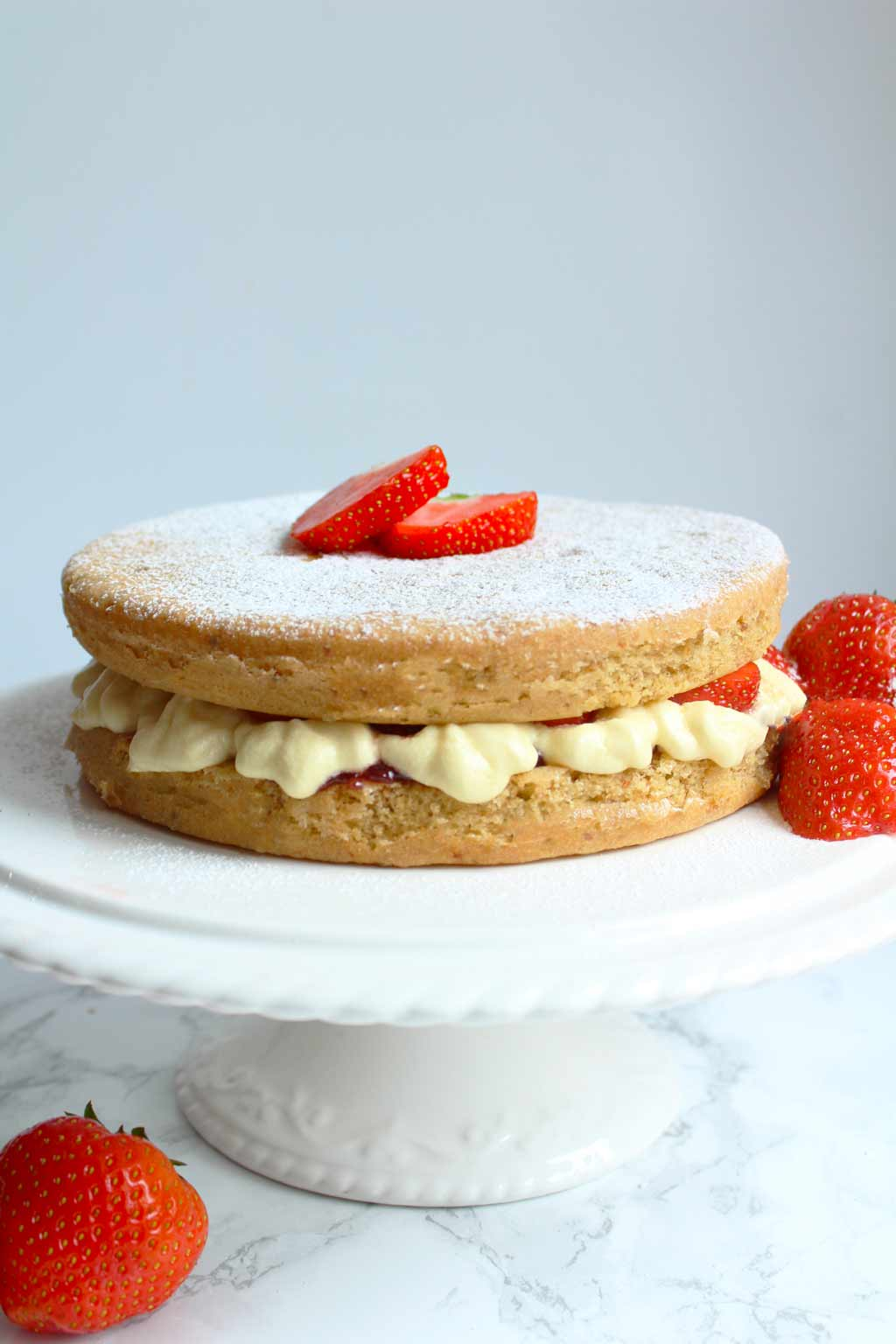 vegan victoria sponge cake on a stand with strawberries