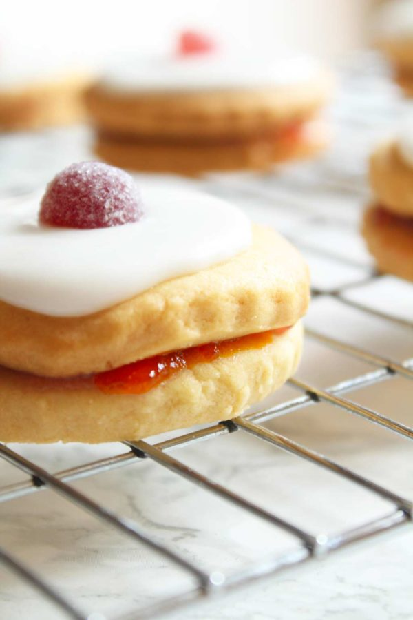iced empire biscuits resting on a wire rack