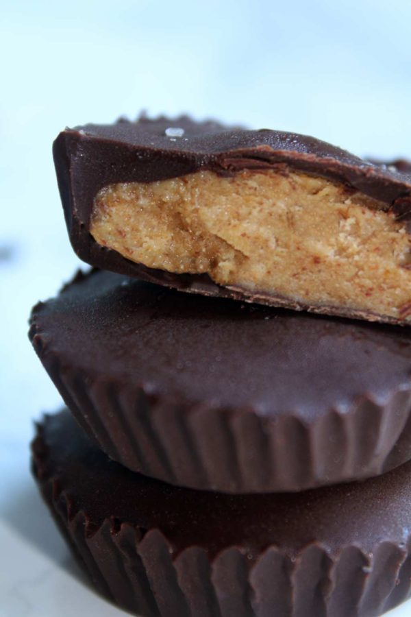 A stack of 3 peanut butter cups. The top one is cut in half and shows the peanut butter filling.