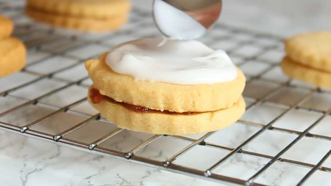 spreading icing on top of the biscuits