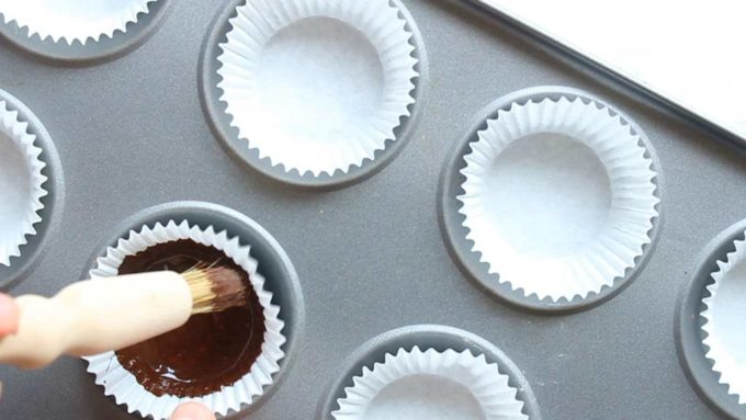 painting the first layer of chocolate onto a paper case