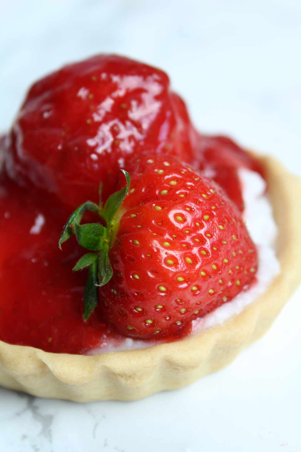 close up of mini fruit tart with a strawberry on top