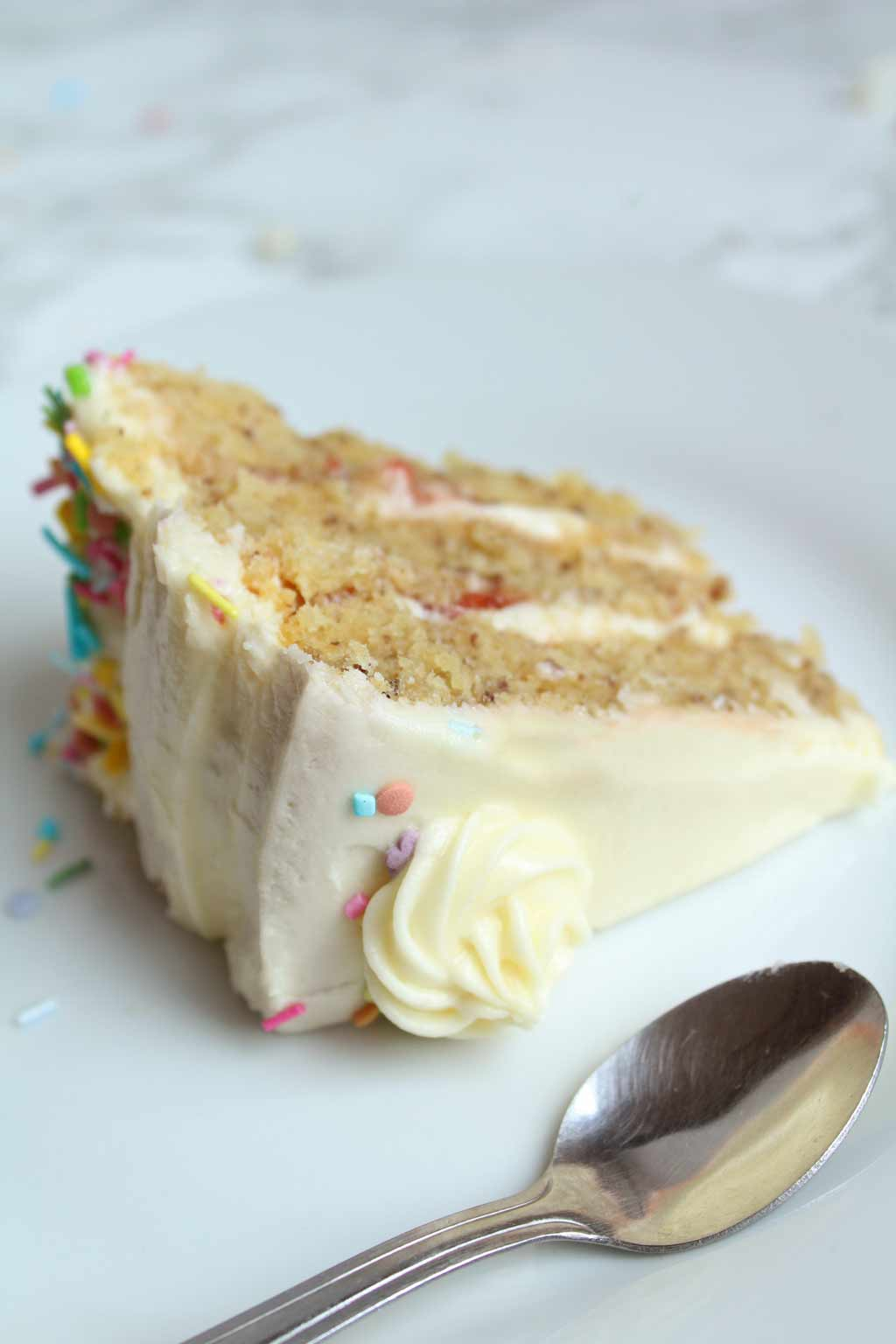 a slice of vegan birthday cake and a spoon on a small plate