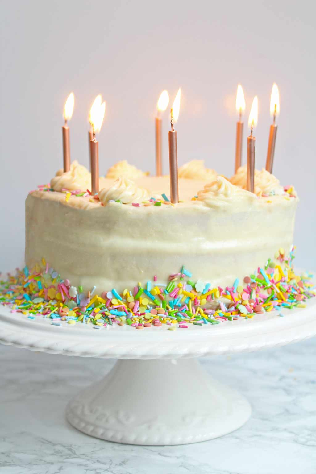 vegan birthday cake on a cake stand with candles lit
