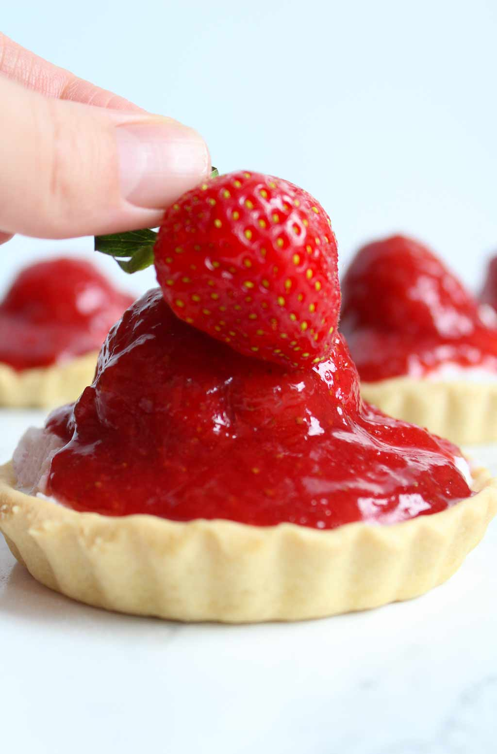 hand placing a strawberry onto the mini tart