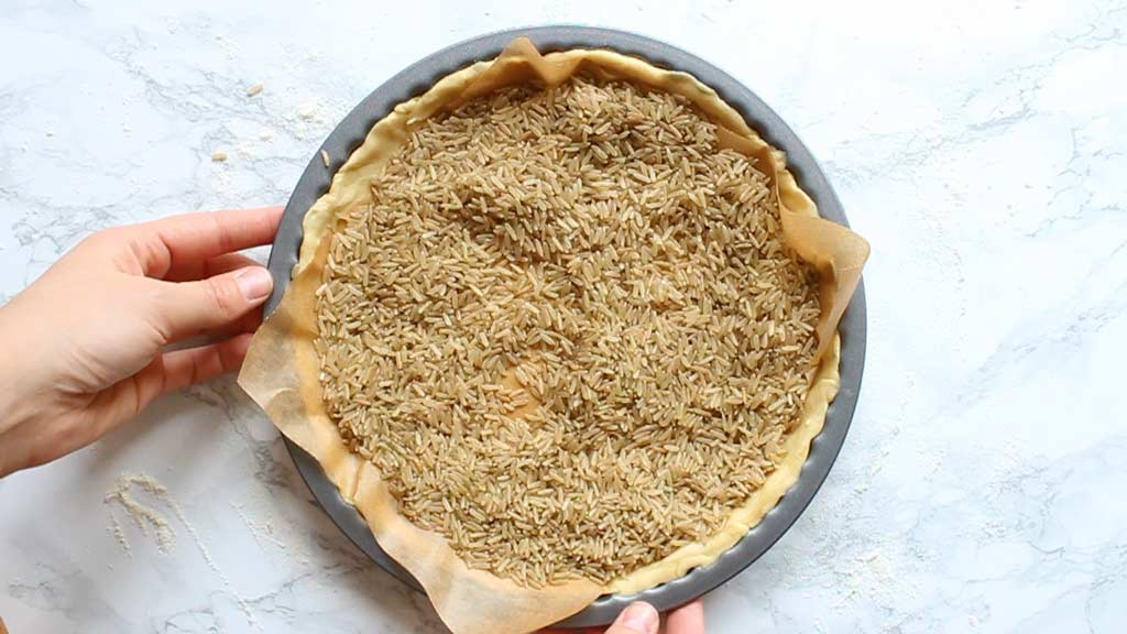 covering the pastry with rice to weigh it down