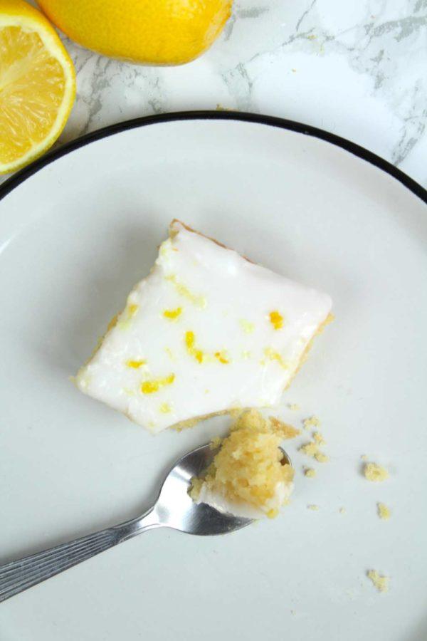 a square of lemon elderflower cake with a teaspoonful of cake beside it