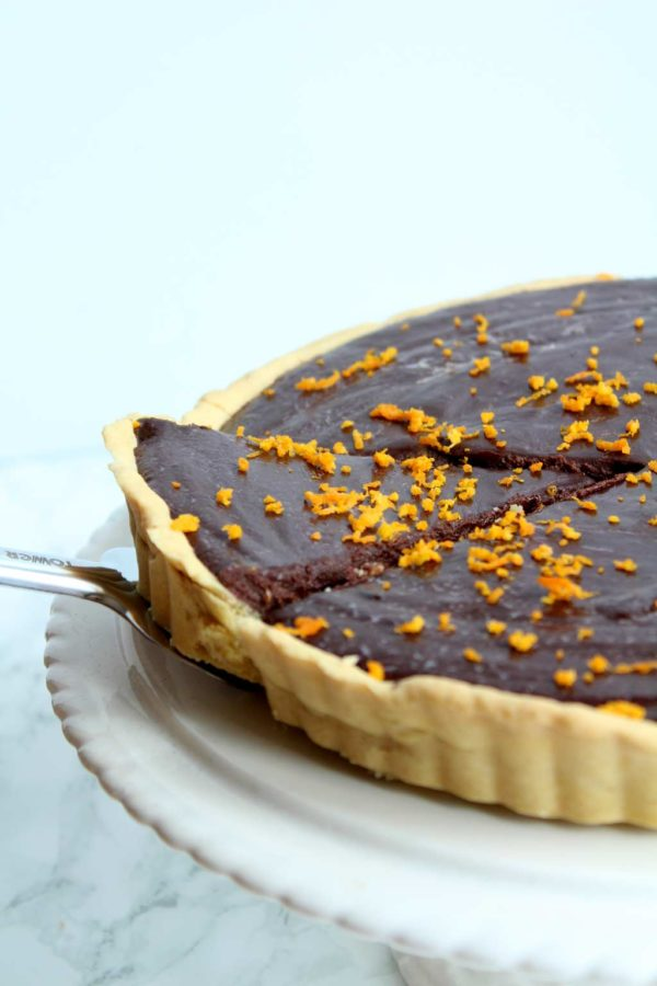 close up of chocolate orange tart. a cake slicer is removing one slice of the tart