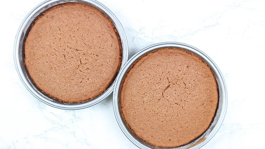 two baked red velvet cakes in cake pans
