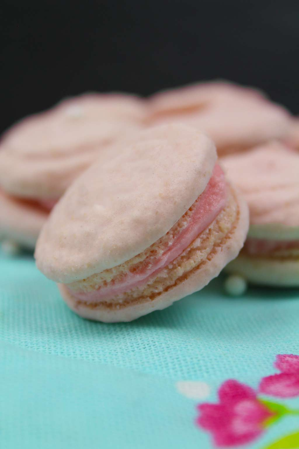 close up of vegan macarons on a pink and blue floral cloth