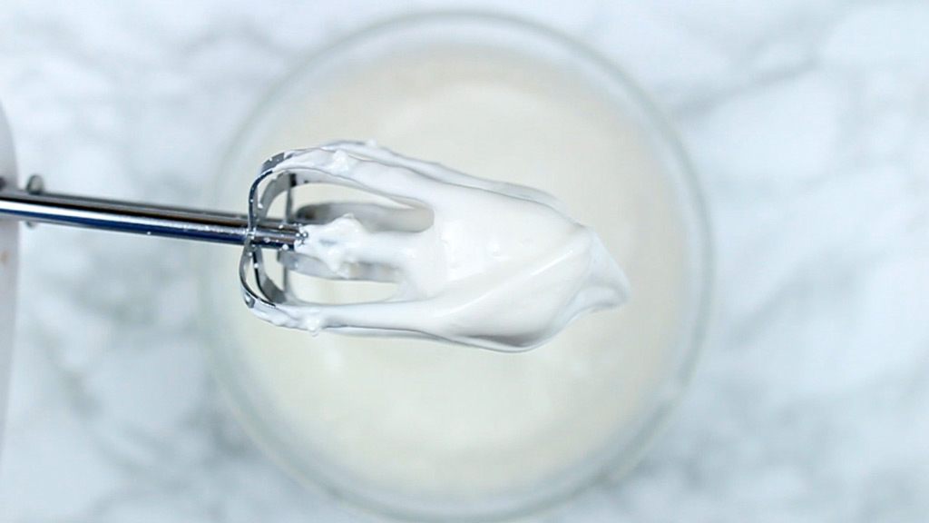 close up of meringue mixture on the end of whisk