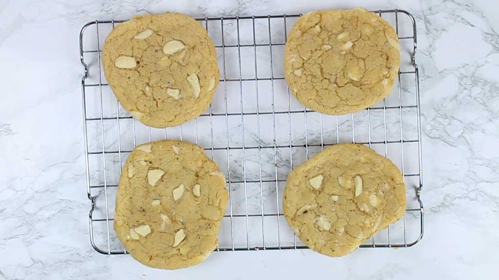 4 white chocolate chip cookies on a cooling rack
