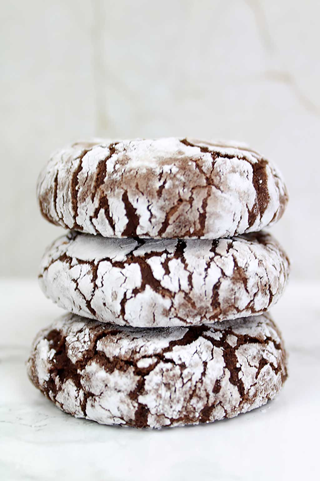 stack of 3 vegan chocolate crinkle cookies with white background