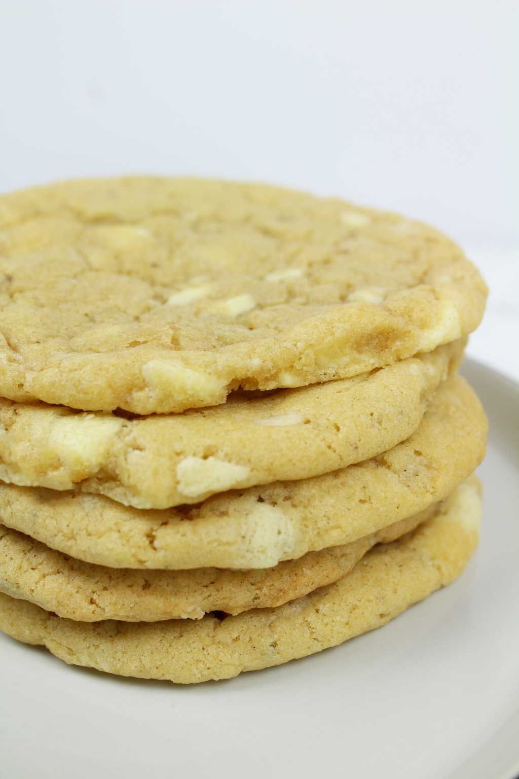 a stack of 5 white chocolate cookies on a plate