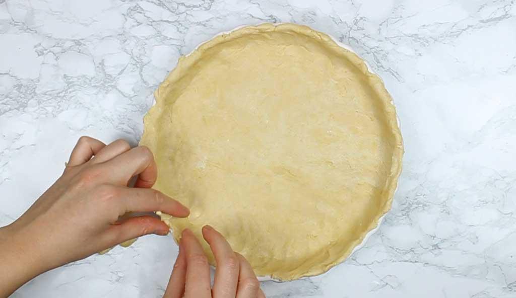 pressing the dough into the tart tin